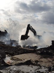 Crews operate a backhoe to extinguish a fire that destroyed