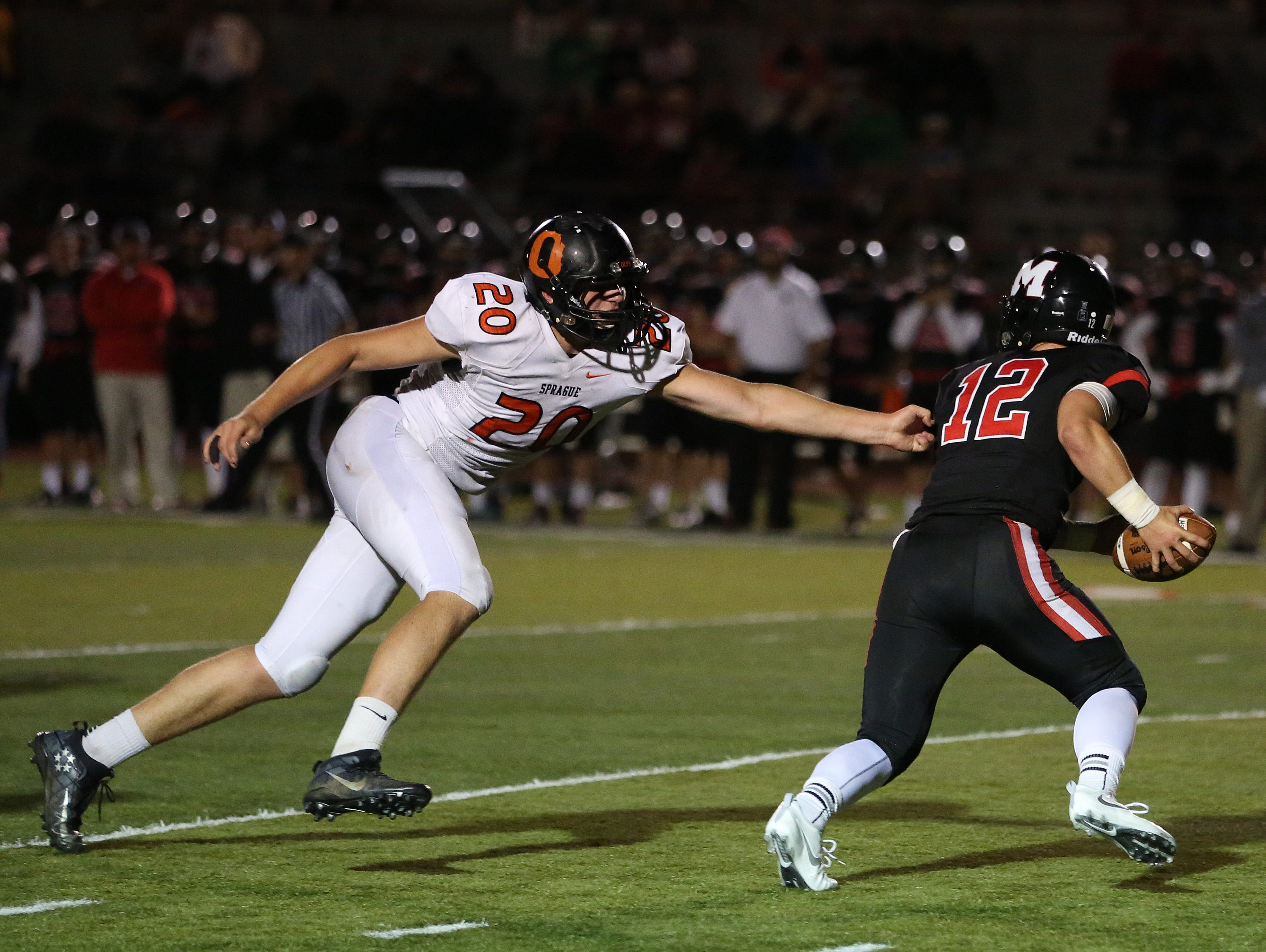Sprague's Teagan Quitoriano goes after McMinnville's Wyatt Smith as the Olys defeat the Grizzlies 49-27 in Greater Valley Conference game on Friday, Sept. 23, 2016, in McMinnville.