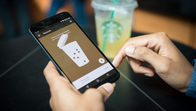 A Starbucks customer uses the mobile phone app to view how many stars are in account.