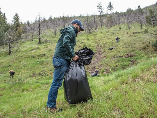 Ben Sauer gathers trash at Skin Gulch in Poudre Canyon