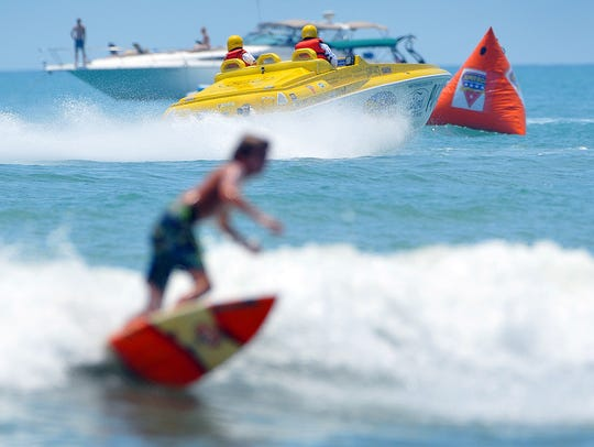 The offshore powerboats attract all kinds of fans, even those surfing really close to shore.