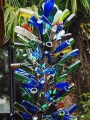 Scores of colorful bottles adorn a 10-foot bottle tree in a courtyard outside Rick Griffin's Jackson home.