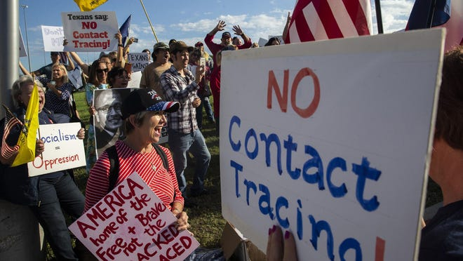 Renata Richardson, center, chants with other demonstrators during a protest organized by Texans Against Contact Tracing outside of the building that houses MTX Group, the company hired by Texas to do contact tracing, in Frisco, Texas, on May 26, 2020.