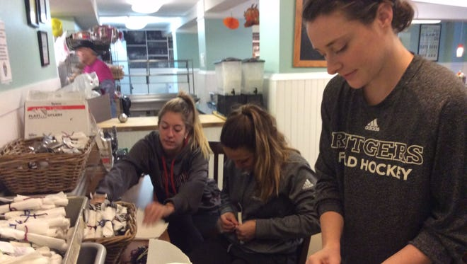 Members of the Rutgers women's field hockey team prepare napkins and utensils for a meal at Elijah's Promise Community Kitchen.