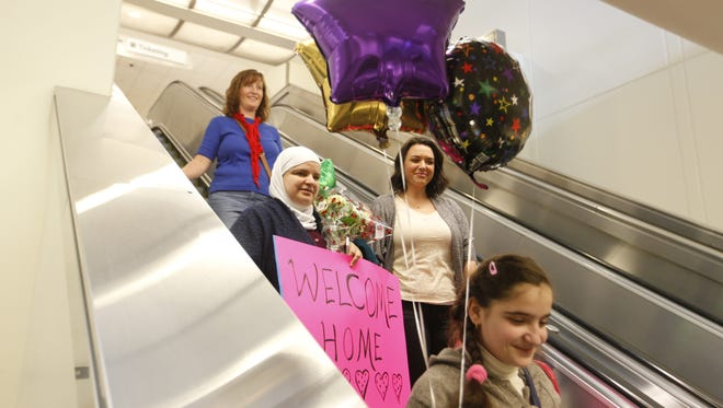 Reem Kabbani, holding sign, her daughter Raghed Haj Omar, foreground and representatives of Kentucky Refugee Ministries made their wahy to baggage claim at Louisville International Airpoert. The Syrian refugee family arrived in Louisville as President Donald Trump gave his inauguration speech. Trump has promised to curtail immigration from Syrian. Jan. 20, 2017.