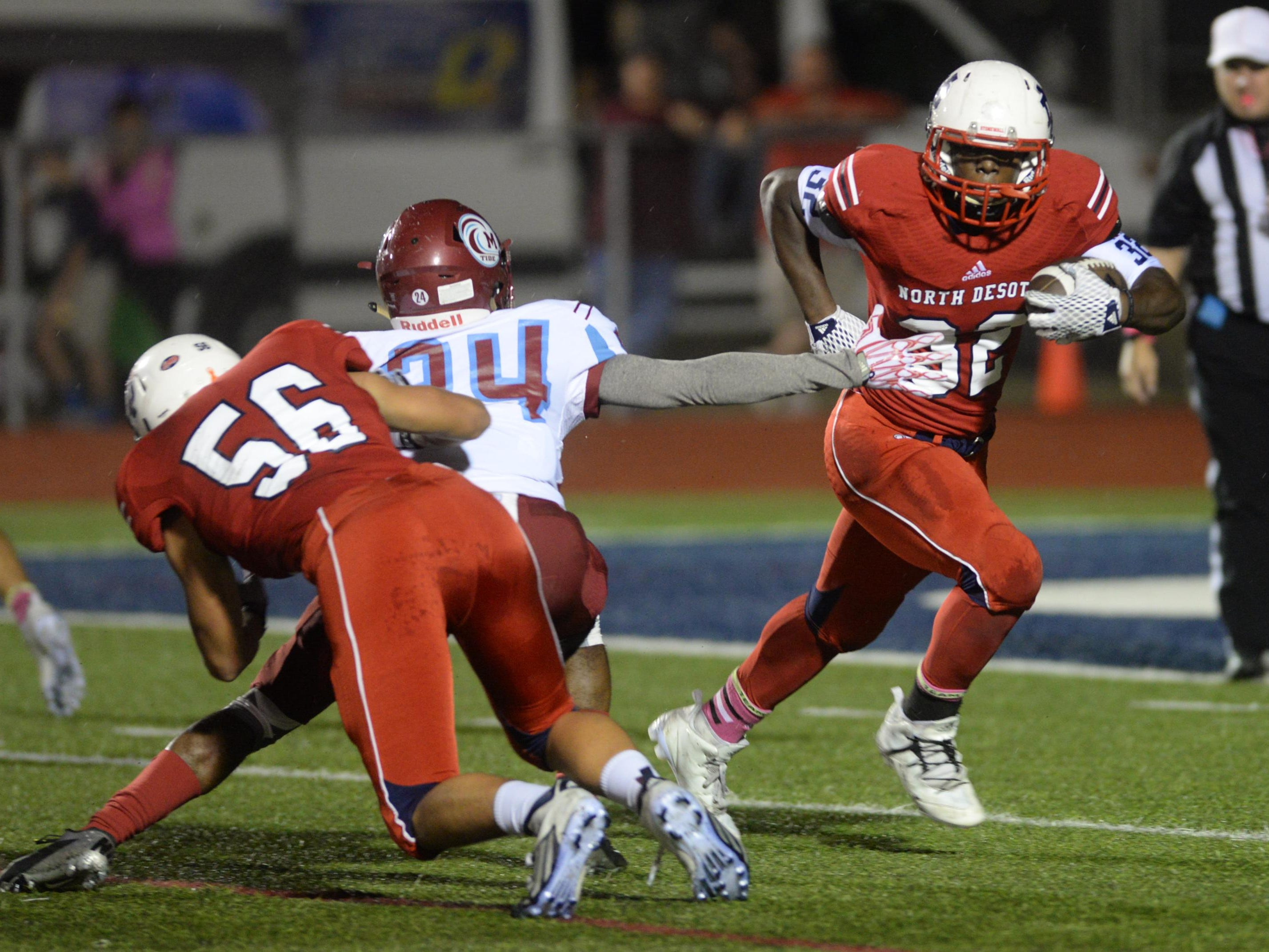 Delmonte Hall of North DeSoto eludes the grasp of Minden's Kenneth Francis during their game Friday.