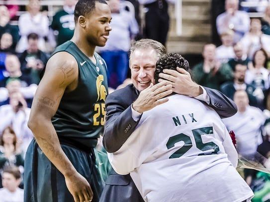 MSU basketball coach Tom Izzo hugs senior Derrick Nix's
