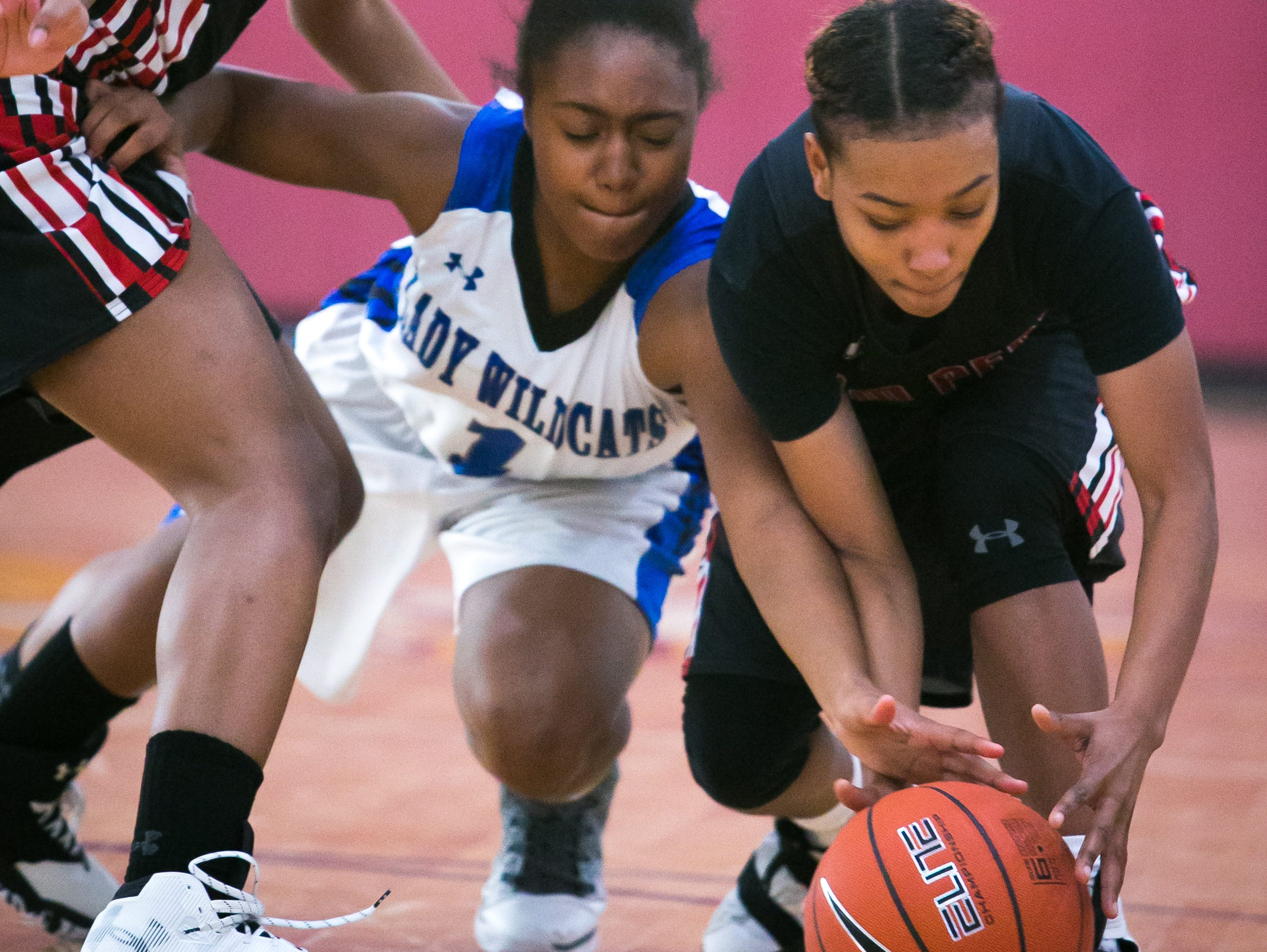William Penn Micah Yarbray (left) and teammate Alize Felton battle for the loose ball with Howard guard Na'Leigha Wright battles for the loose ball in the second half. William Penn loses to Howard high with a final score of 43-32.