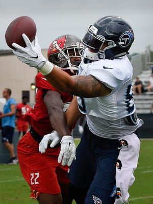 Titans tight end Jerome Cunningham (89) pulls in a pass over Buccaneers defensive back Josh Liddell (22) during a joint practice Thursday at Saint Thomas Sports Park.