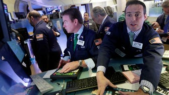 Specialists work at their posts on the floor of the New York Stock Exchange.