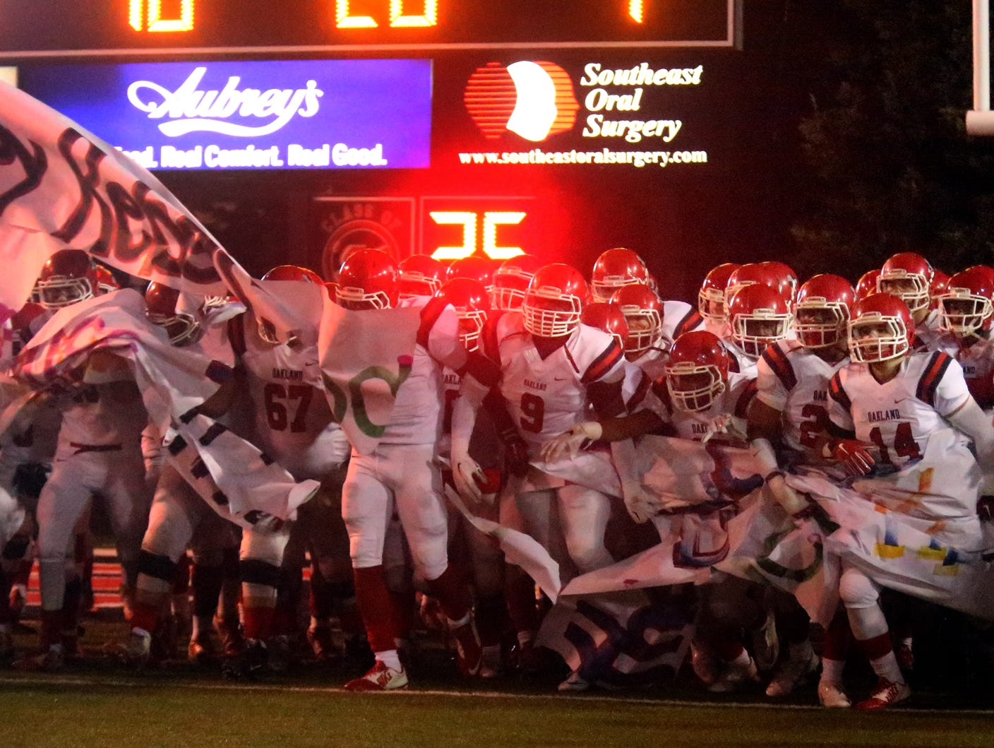 The Oakland football team breaks through a banner to run onto the field Friday.