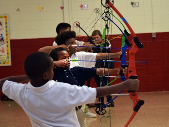 Alma Redwine Elementary students practice archery during