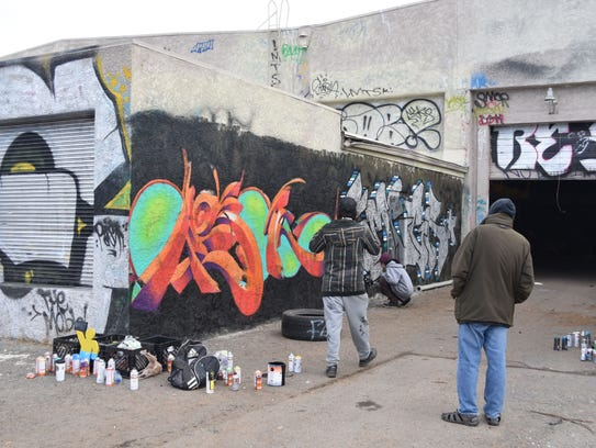 A submitted photo of two individuals looking at graffiti