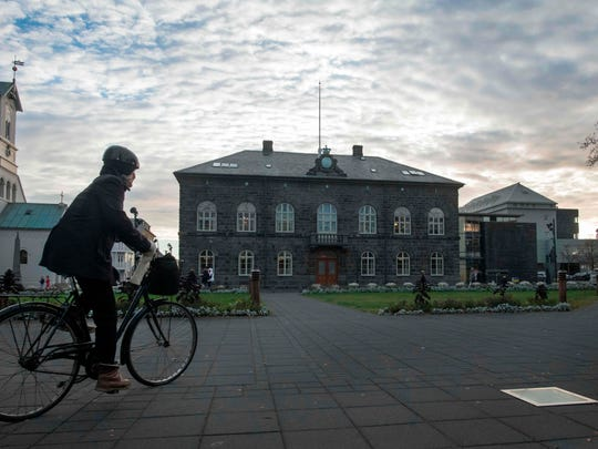 A woman bicycles past the Althingi Parliament building