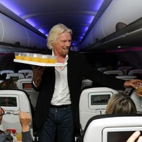 Virgin Group founder Richard Branson passes out beverages to guests aboard Virgin America Flight 11 from New York to San Francisco as part of an airline promotion on Sept. 19, 2012.