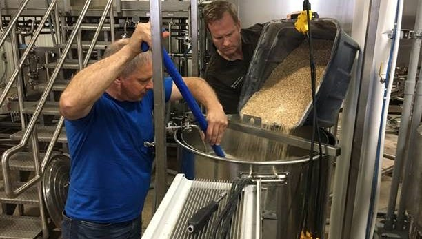 Kohler Festival of Beer Homebrew winners Terry Andersen and Mike Coulson pour in the base malt for their Hula Girl Coconut Stout on July 5 at 3 Sheeps Brewing Company.