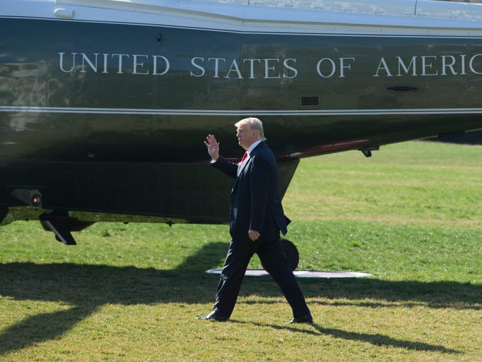 Trump waves while walking across the South Lawn of