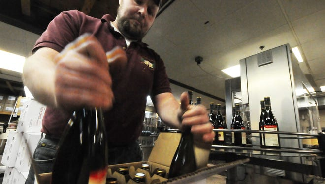 Chad Simon boxes wine off the bottling machine at Door Peninsula Winery.