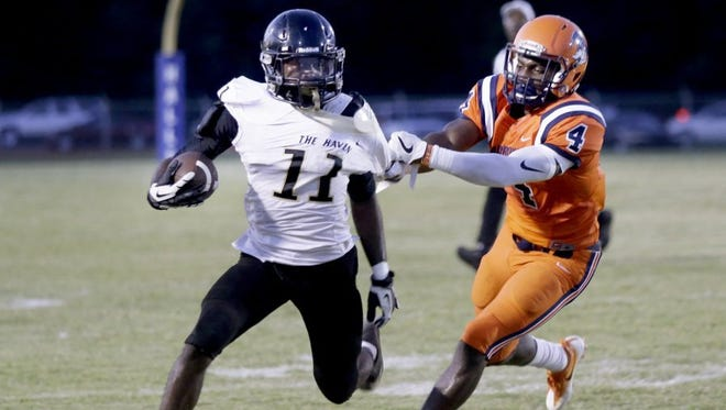 Whitehaven running back Kylan Watkins, who scored three touchdowns in the No. 1 Tigers' 27-8 victory over previously unbeaten and third-ranked Ridgeway on Friday night at Halle Stadium, tries to get away from the Roadrunners' Noah Spann.
