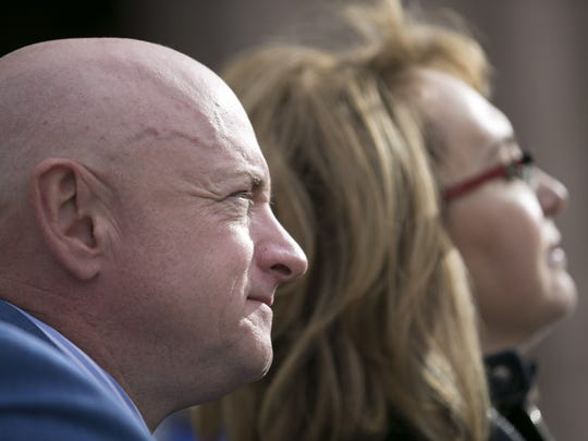 Former astronaut Mark Kelly and his wife, former U.S. Rep. Gabrielle Giffords, look on during the memorial dedication at El Presidio Park in Tucson on Monday, Jan. 8, 2018. The dedication was held on the 7 year anniversary of the Tucson mass shooting that left 6 people dead and 13 others injured including Giffords. The memorial is expected to be completed within the next two years.