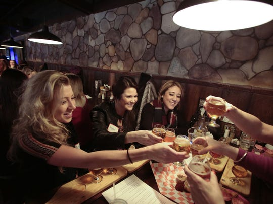 Ashley Sword, left, Angela Wszola and Chanel Jackson, all of Dearborn, toast at Girls' Pint Out in Taylor.