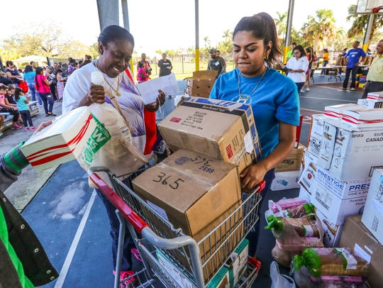 Glenda Leiva, of Cape Coral , gets help from Adrianna Lazarin, 16 of Fort Myers and a volunteer at Nations, with turkey and fixings Saturday. This was part of a city-to-city Irma relief event coordinated by Nations Association.
