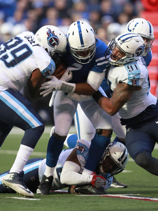 FILE - In this Nov. 26, 2017, file photo, Indianapolis Colts quarterback Jacoby Brissett (7) is sacked by Tennessee Titans defensive end Jurrell Casey (99) and outside linebacker Derrick Morgan (91) during an NFL football game, in Indianapolis.  Tennessee linebacker Wesley Woodyard went vegetarian after finally getting a taste of the delicious burgers his teammates ate in the locker room. He has plenty of company on defense too with 11 Titans jumping on the plant-based diet with lunches delivered by the Cordon Bleu-trained wife of linebacker Derrick Morgan. (AP Photo/Jeff Haynes, File)