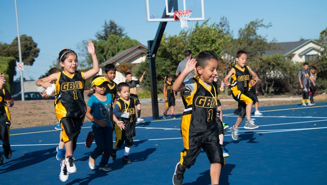 Children with Gil Basketball Academy run across newly-refurbished basketball courts at Cesar Chavez Park in Salinas.