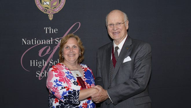 Dana Krejcarek, Kohler high school science teacher, shakes hands with Claes Nobel, senior member of the family that established the Nobel Prize and Chairman of the National Society of High School Scholars. Krejcarek was named to the 2015 Claes Nobel Top 10 Educators of the Year list.
