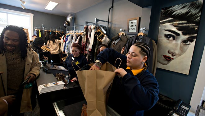 Karina Ramos bags a customer's purchase at Thrift Works, a store that teaches young people retail and entrepreneurial skills.