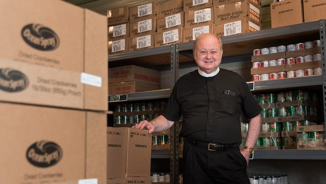 Rev. Dr. John Riley poses for a photo inside the food storage area for a USDA food distribution program sponsored by the Smyrna-Clayton Ministerium at the Smyrna First Presbyterian Church in Smyrna on Wednesday.