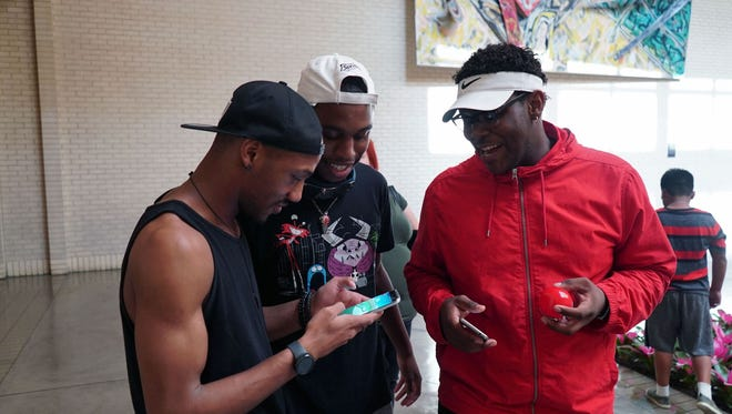 From left, Trayvon Washington, 20, plays Pokemon Go while his friends Casey Jones, 20, and Dre Horton, 19, watch, while walking around the NorthGate Center mall in Dallas.