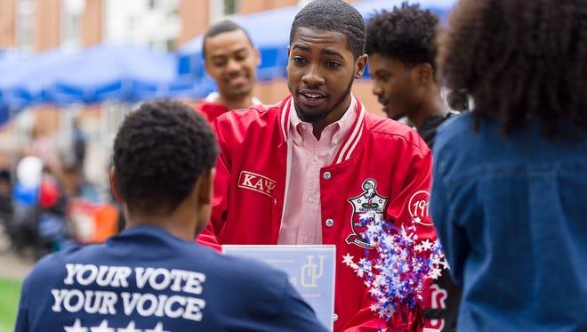 University of Delaware senior Christopher Bell registers to vote at the UDecide 2016 voter registration drive on Monday. Tuesday is National Voter Registration Day.