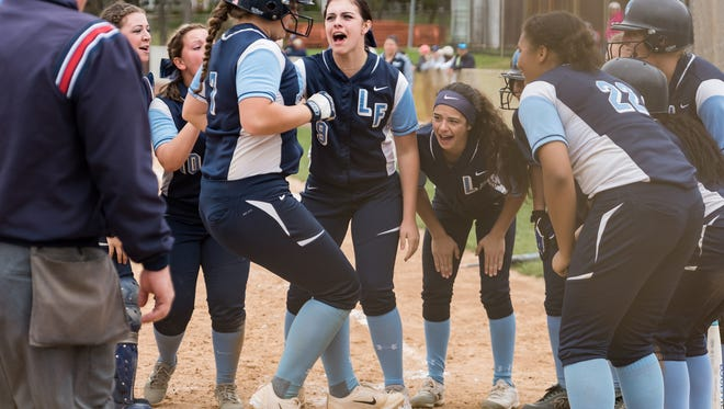 Brooke Glanden of Lake Forest is welcomed at home plate after hitting a grand slam against Caravel on April 15. The Spartans moved up to No. 1 statewide in the final News Journal rankings before the state tournament.