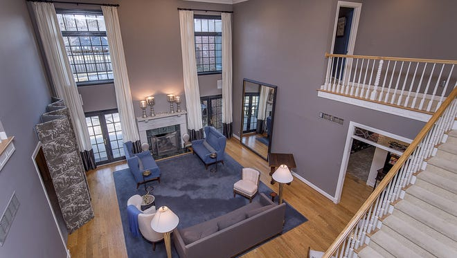 The two-story great room features floor-to-ceiling windows and a gas fireplace.