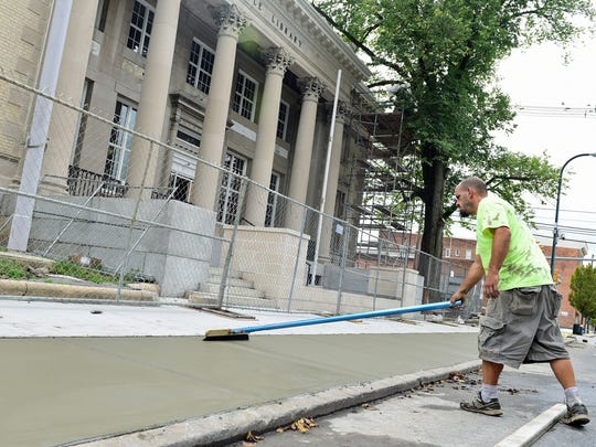 Eddie Arnold, of Pro's Concrete, Fayetteville, lays a new sidewalk in front of Coyle Free Library on Tuesday, October 10, 2017. The extension and remodeling project ben May 2016 and comes to a close next month. The project more than doubles the library's 12,000-square-foot footprint to about 29,000 square feet, complete with reinforced cornices on the exterior of the building,  and a garden terrace on the roof at one end of the building's extensions.