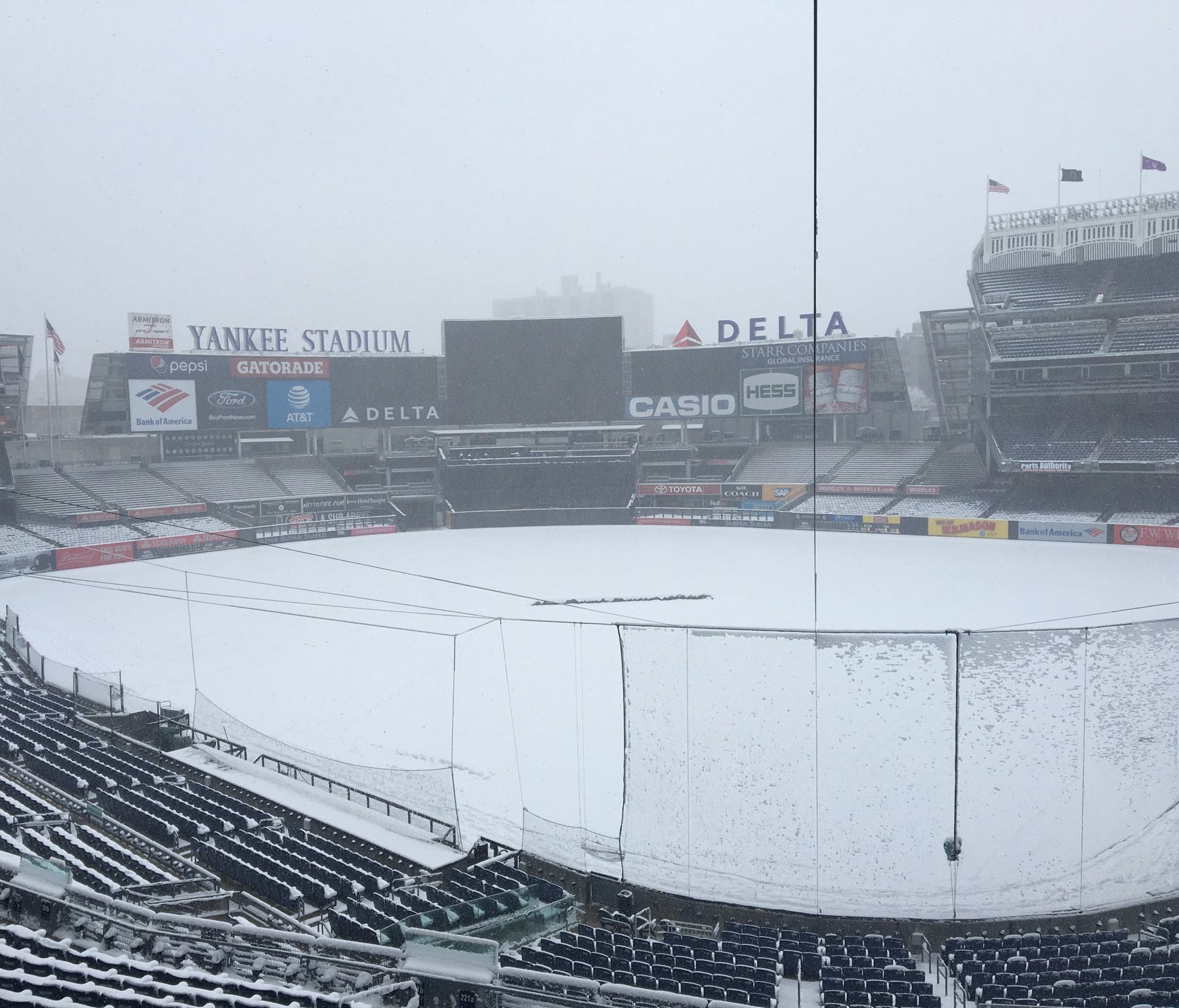 Snow blankets Yankee Stadium, postponing the team's home opener a day.