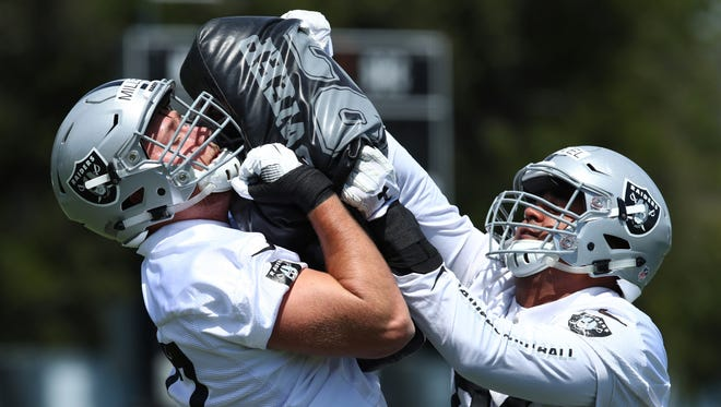 The Oakland Raiders' Kolton Miller (left) blocks during rookie minicamp in Alameda, Calif.