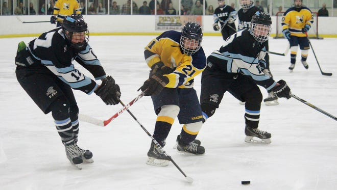 Colton Shan (21) of Toms River North battles for a loose puck with Toms River East defenders.