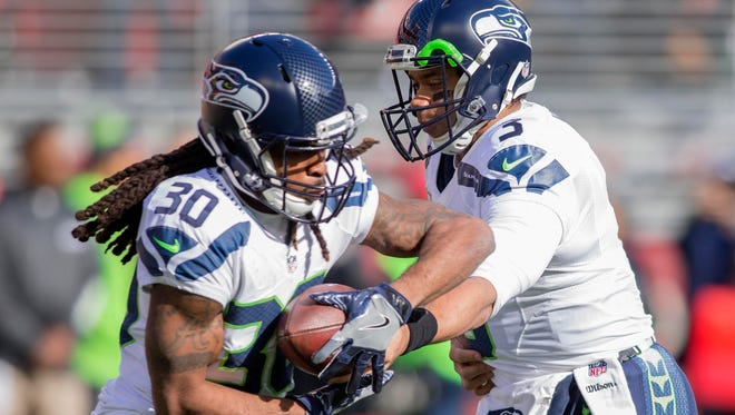 Seahawks running back/kick returner J.D. McKissic (left) takes a handoff from quarterback Russell Wilson during warm-ups for the regular-season finale in San Francisco.