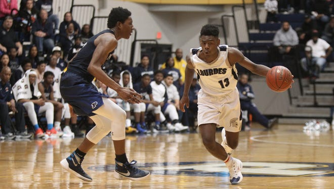 Lourdes' Kevin Townes dribbles up court against Poughkeepsie during a Class A regional final on March 11, 2017.