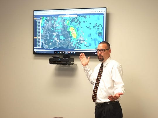 National Storm Center Executive Director Dave Carlson points to an image on the monitor during a demo Wednesday morning in the weather company's Fort Walton Beach station.