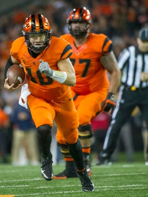 Oct 8, 2016; Corvallis, OR, USA; Oregon State quarterback Darell Garretson (10) carries the ball as offensive lineman Sean Harlow (77) looks on against the California during the second quarter at Reser Stadium. Mandatory Credit: Cole Elsasser-USA TODAY Sports