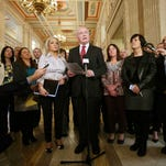 Sinn Fein's Martin McGuinness, centre, stands with members of his party during a press conference at Stormont Parliament in Belfast, Northern Ireland, Tuesday, Oct. 20, 2015 as he gives his reaction in the wake of the publication of a Government-ordered review of paramilitary structures in Northern Ireland. An expert report into the current state of the Irish Republican Army and other outlawed Northern Ireland groups has found that the IRA still exists and some members still pursue violence and crime, but as an organization the group poses no threat to peacemaking. (Niall Carson/PA via AP) UNITED KINGDOM OUT NO SALES NO ARCHIVE