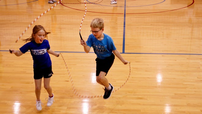 """Ella Beck, 8, and Sam Gauger, 9, practice a move called the """"wheel"""" during a practice for Indy Air Bears, a jump roping group, at Arlington Elementary School in Indianapolis on Monday, Aug. 18, 2014."""