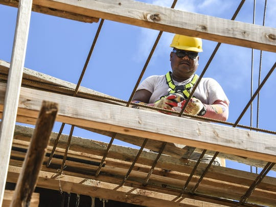 In this Oct. 4, 2016, file photo, carpenter Negs Barrozo prepares to fasten lumber together into a form, as he and other 5M Construction Corporation employees work at a building project in Tamuning. A near 100-percent rejection rate for Guam H-2 worker visa applications has short- and long-term implications for the island's construction industry Carpenter Negs Barrozo prepares to fasten lumber together into a form, as he and other 5M Construction Corporation employees, work at a building project in Tamuning on Tuesday, Oct. 4. 5M is one of a dozen Guam businesses that sued the federal government over worker visas.