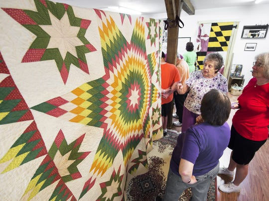 A Civil War-era quilt owned by Beverly Scavone, top left, of Freeland, Maryland, was on display during a community celebration at the newly opened Teaching Museum for the Fiber Arts and Textiles. The quilt was made by Scavone's great-grandmother