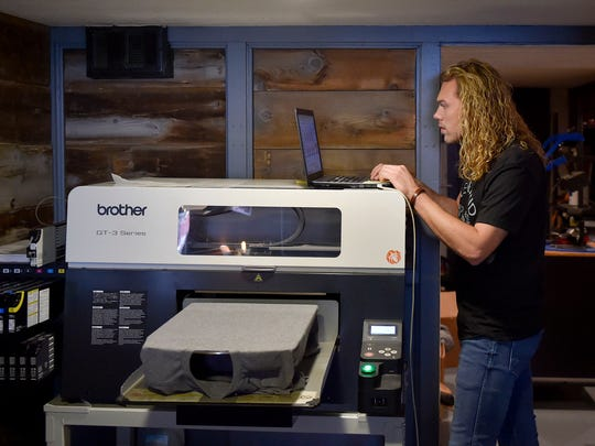 Brett Jolliff waits for the printer to complete a job, printing a T-shirt with a custom design by Jolliff.