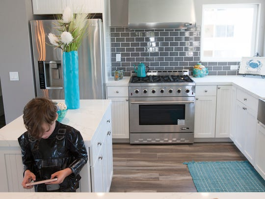 Max Carlson plays a video game on his phone in the kitchen of a home for sale in Hollywood Beach. Max's parents, Andrew and Sara Carlson, were looking at the home during a recent open house.
