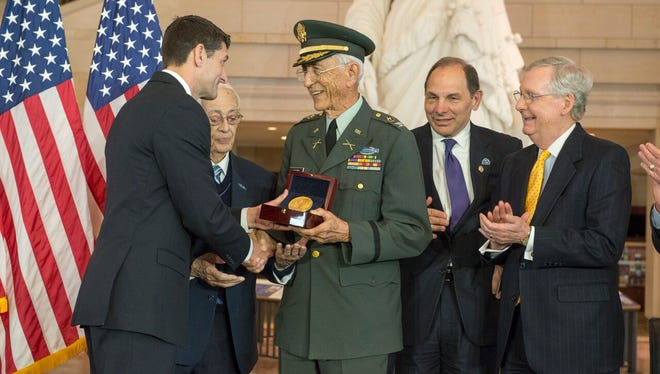 Col. Manuel F. Siverio Sr., a veteran of the former all-Puerto Rican 65th Infantry Regiment, known as the Borinqueneers, accepts the Congressional Gold Medal from House Speaker Paul Ryan at the U.S. Capitol on April 13, 2016. To Siverio's right are Veterans Affairs Secretary Robert McDonald and Senate Majority Leader Mitch McConnell.